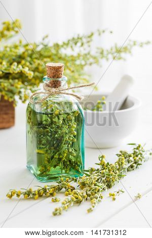 Bottle Of Absent Or Tincture Of Tarragon, Absinthe Healing Herbs And Mortar On White Table. Herbal M