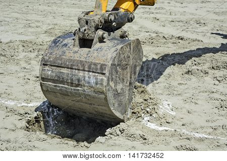 Excavator in a situation digs holes in the sandy ground.