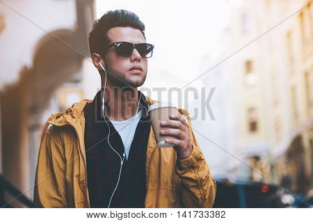 City lifestyle. Handsome young man in headphones carrying coffee cup while walking along the city street