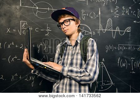 Education, high school, college. Portrait of a student boy standing by a school blackboard.