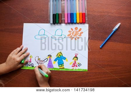 child draws his large family. Only visible hand