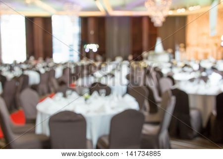 blur tables and chairs set up for a wedding banquet
