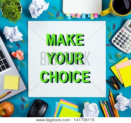 Make your choice. Office table with notepad, computer and coffee cup on blue background. Business creative consept top view