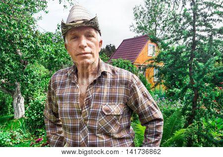 Portraitn senior farmer the background of the house and garden