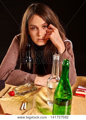 Drinking girl in depression drinking alcohol and smokes cigarettes in solitude. Drinking habits. Girl is heavy drinkers. Girl looks in camera.