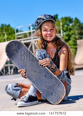 Teen skateboard girl sitting on his skateboard outdoor. Skateboard sport for extrem girl.