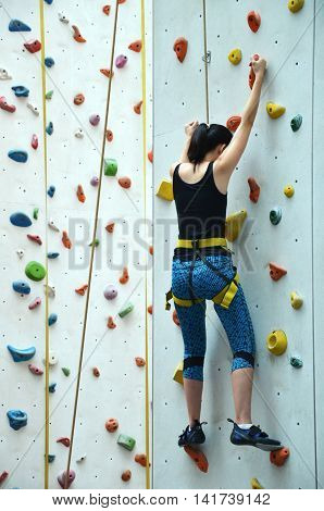 SINGAPORE - 30 JULY 2016: Rave teenage with harness climbing vertical wall teenage confidence concept.
