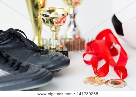 sport, achievement, championship and success concept - close up of football or soccer boots with golden medals and cups
