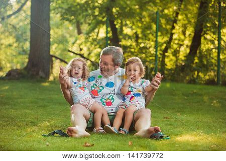 Portrait Of Grandfather With Granddaughters against green grass
