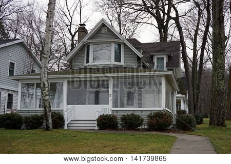 WEQUENTONSING, MICHIGAN / UNITED STATES - DECEMBER 22, 2015: The front porch of a white home, on Beach Drive in Wequetonsing, is protected from the winter weather.