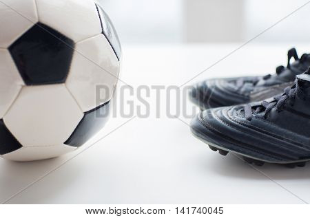 sport, soccer, football and sports equipment concept - close up of ball and boots on table