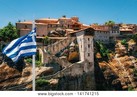 Greek flag in front of The Holy Monastery of Great Meteoron in Meteora - complex of Orthodox monasteries on mountains Thessaly Greece