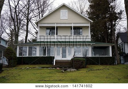 WEQUETONSING, MICHIGAN / UNITED STATES - DECEMBER 22, 2015: A home with an enclosed front porch and a balcony on Beach Drive in Wequetonsing.