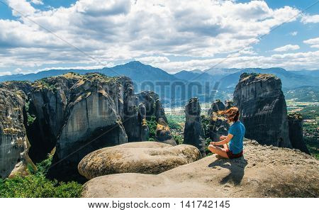 Girl sitting on the view point of the mountain concept of travelling happiness freedom. Traveler enjoying the mountain landscape of Meteora Greece
