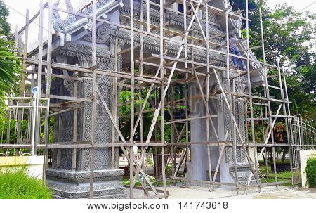 Buddhist temple gate covered with wooden scaffolding while under repair, in Songkhla, Thailand