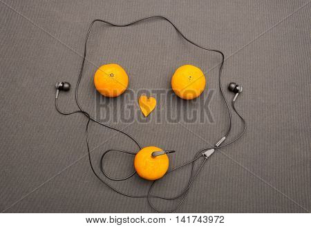 Funny fruity music player: headphones coming from of mandarin on a black background. Small orange heart and two mandarins lying near him in the form of face. Present for music and fruit lovers.