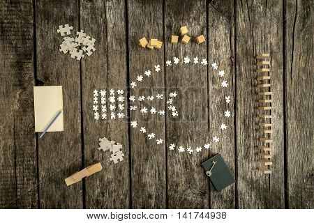 Various white puzzle pieces formed in shapes on table alongside blocks cubes notepad and key.