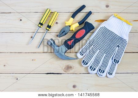 Gloves and tools on wooden table taken in top view