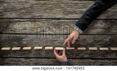 Fingers walking across planks with hand underneath over wooden surface for concept about deception in business.