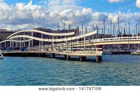 Barcelona Spain - April 3 2016: Rambla de Mar and Port Vell in Barcelona city. Crowd of people walking across the swing bridge on the Rambla de Mar. The Ramla del Mar is a main tourist attraction in Barcelona. Spain