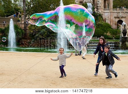 Barcelona Spain - April 4 2016: Children enjoy the soap bubbles in the in the Ciutadella Park in Barcelona. Ciutadella park is one of the finest parks in Barcelona. Park dotted with historic landmarks statues and fountains