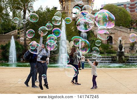 Barcelona Spain - April 4 2016: People catching the soap bubbles in the in the Ciutadella Park in Barcelona. Ciutadella park is one of the finest parks in Barcelona. Park dotted with historic landmarks statues and fountains