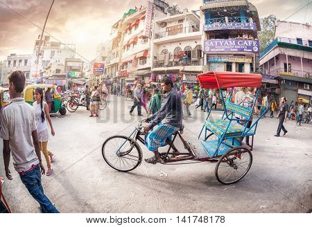 NEW DELHI INDIA - FEBRUARY 23 2015: Rickshaw driver at crowded street with shops hotels transport and people in Main Bazaar Paharganj