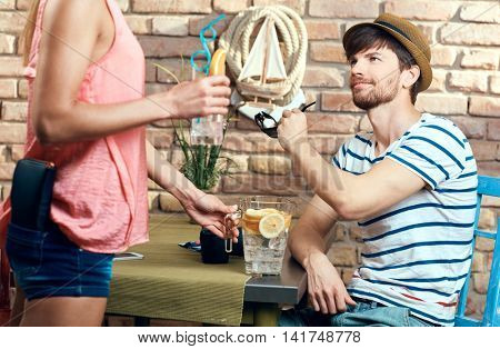 Waitress serving young man in bar at summertime.