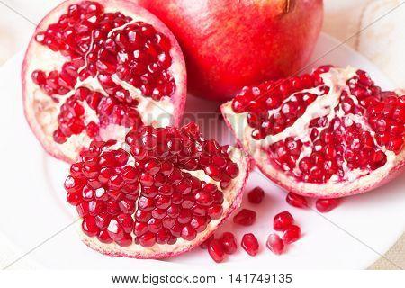 Closeup sliced pomegranate on a white plate