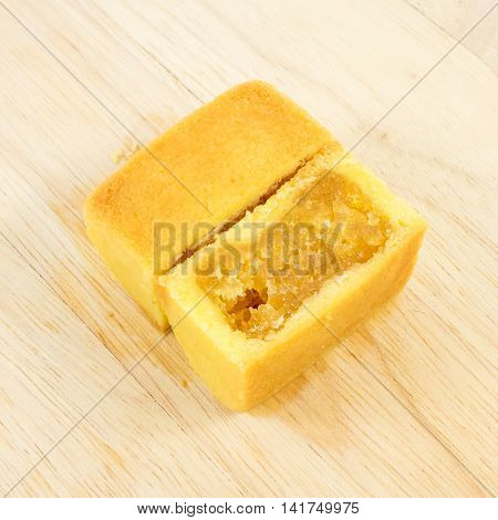 The tasty Taiwanese pineapple pastry cake with egg yolk on the wooden plank.