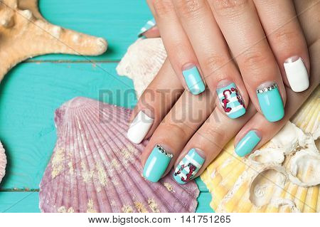 French manicure - beautiful manicured female hands with marine manicure with rhinestones on background seashells and starfish