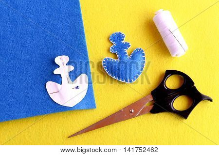 Home made anchor. Blue felt anchor is sewn with white thread, needle, paper pattern pinned on a flat piece of blue felt, scissors on a yellow background. Sewing instruction for children. Step