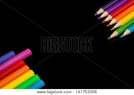 Lots of assorted colors marker pens and pencils with copyspace on black glass background