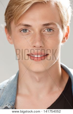 Close up portrait of handsome cheerful blond young man wearing casual black t-shirt and jeans jacket looking in camera on grey background. Copy space