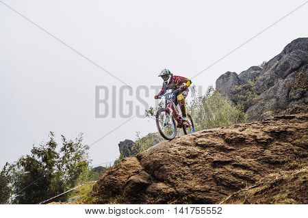 Magnitogorsk Russia - July 23 2016: male young driver athlete on bike at edge of cliff during National championship downhill