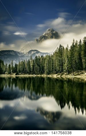 Mountain landscape with lake in the front fog engulfing the peak and dramatic light above. Wilderness raw nature concept and background. Antorno Dolomites Italy.
