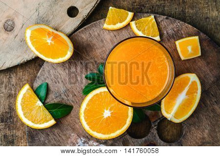 Orange juice with orange pulp on rustic wooden table