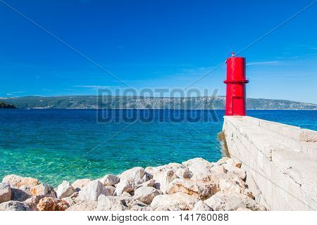 Red lighthouse on the Cres Island in Croatia, seascape, sunny summer day