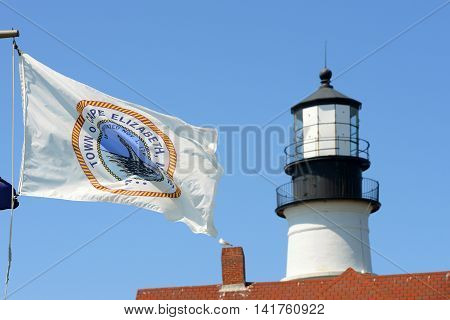 Flag of Town of Cape Elizabeth with Portland Head Lighthouse at the background, Cape Elizabeth, Maine, USA. This lighthouse was built in 1791, and is the oldest lighthouse in Maine.