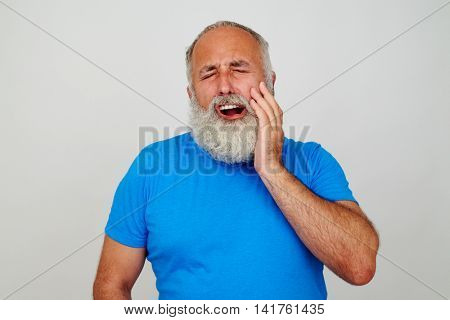 Bearded male in blue T-shirt is touching his cheek as if suffering from toothache isolated against white background