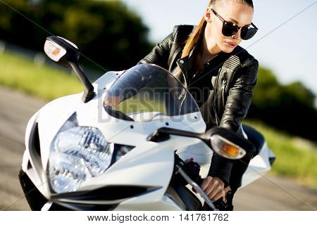 Pretty young woman riding on the motorcycle