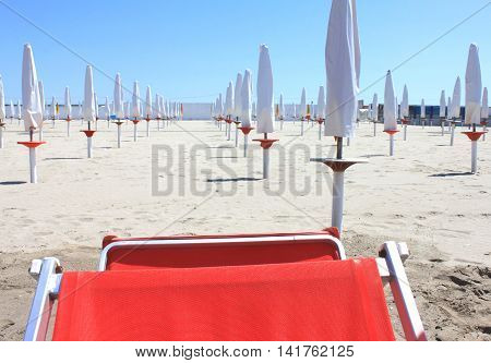 deckchair and beach umbrellas on a sandy beach