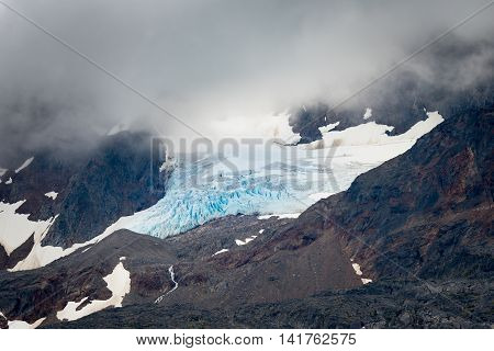 Large blue iceberg draped in fog on a mountain peak near Skagway AK
