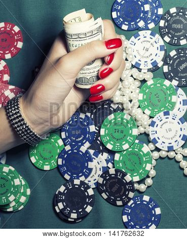 hands of young caucasian woman with red manicure at casino green table close up, luxury jewelry