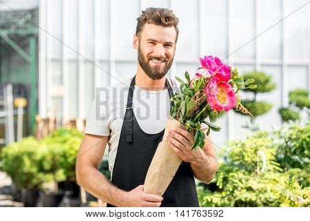 Portrait of a handsome flower seller holding a beautiful bouquet with pink peonies in the shop