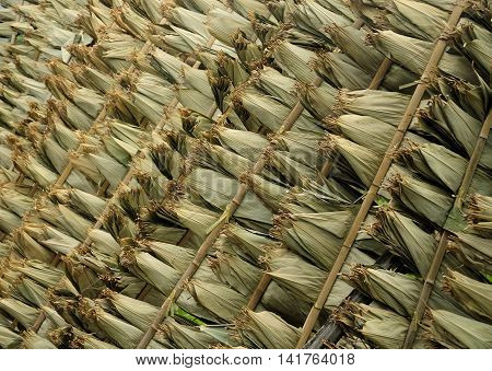 Dried corn husks drying outside on a bamboo rack used for a chinese dish called zongzi which is rice and meat wrapped up in a corn leaves and steamed in a steamer.