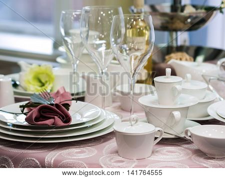 Set of new dishes on table with tablecloth. Stack of white plates and wine glasses on restaurant table. Shallow DOF