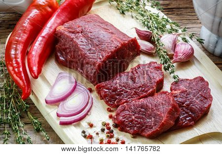 Beef tenderloin on a cutting board. Fresh raw meat for cooking dinner. Condiments and spices on the table