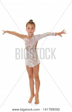 -Isolated on white backgroundCute barefoot girl gymnast in pink dress . Girl holding hands near the face-Isolated on white background
