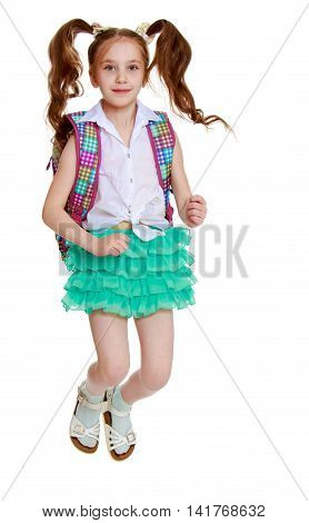 Joyful little girl with long hair to the waist which wire braided white ribbons. In a white shirt without a pattern and green short skirt. Girl jumping with legs tucked under .